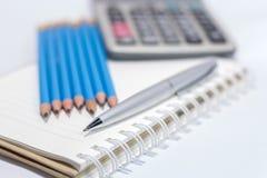 Penna e calcolatore del cavo sul libro Immagini Stock