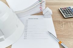 Penna e cappello bianco dell'ingegnere con la lista di controllo sulla tavola di legno Immagine Stock