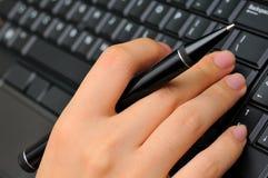 Penna e digitare di holding della mano immagine stock libera da diritti