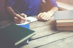 Penna e libri della mano dell'uomo Immagine Stock