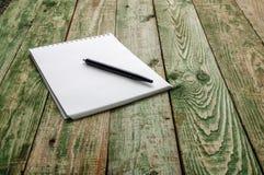 Penna e nota nere sulla tavola di legno verde Fotografia Stock Libera da Diritti
