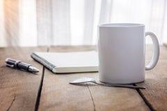Penna e taccuino con la tazza di caffè su di legno Immagini Stock