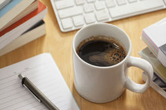 Penna e taccuino del witth del caffè sulla tavola di funzionamento Immagini Stock Libere da Diritti