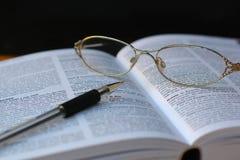 Penna e vetri alla pagina del libro Immagini Stock