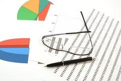 Penna e vetri di Ballpoint sui grafici dei guadagni Fotografie Stock