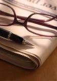 Penna e vetri sul giornale Fotografie Stock