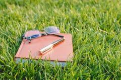 Penna, exponeringsglas och anteckningsbok på gräs Royaltyfri Fotografi