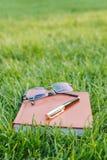 Penna, exponeringsglas och anteckningsbok på gräs Royaltyfria Bilder