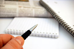 penna för 5 anteckningsböcker för bakgrundsholdingtidning royaltyfri fotografi