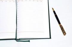 penna för affärsdagbokguld Arkivfoto