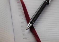 Penna för bollpunkt på bakgrunden av en anteckningsbok med den röda bokmärken royaltyfri fotografi