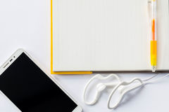 Penna gialla su un taccuino e su un telefono cellulare con il trasduttore auricolare Fotografia Stock