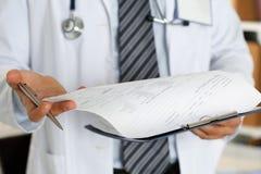 Penna maschio dell'argento della tenuta della mano di medico della medicina che guarda in clipboar Immagini Stock