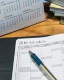Penna med den öppna schemaboken med kalendern på trätabellen Royaltyfri Bild