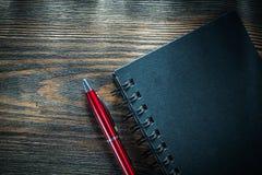 Penna nera del biro del blocco note a spirale sul bordo di legno d'annata fotografie stock libere da diritti