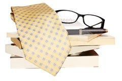 Penna, obiettivo, mucchio dei libri e legame fotografie stock