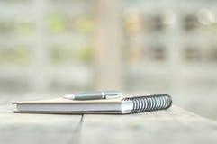 penna och anteckningsbok på det wood skrivbordet Royaltyfri Bild