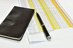 Penna och dokument för svartanteckningsbokonFotografering för Bildbyråer
