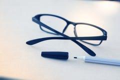 Penna och exponeringsglas på vitbok i blå signal royaltyfria bilder