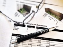 Penna och exponeringsglas som lägger på en rapport med statistik Royaltyfri Fotografi