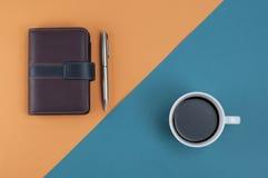 Penna och kaffe för anmärkningsbok på apelsinkorsljus - blått Royaltyfria Foton