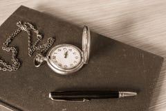 Penna och klocka på böcker royaltyfria foton