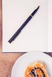 Penna och notepad vid söt mat i platta Royaltyfri Foto