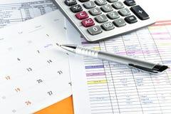Penna och räknemaskin som förläggas på möteplan i kalender Arkivbild