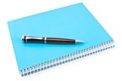 Penna på den blåa spiralanteckningsboken Fotografering för Bildbyråer