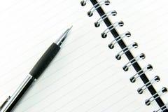Penna på den kontrollerade anteckningsboken Royaltyfria Bilder