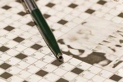 Penna på ett korsord Arkivfoto