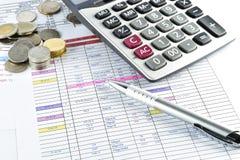 Penna, pengar och räknemaskin som förläggas på dokument Arkivfoto