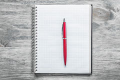 Penna rossa controllata del blocco note in bianco sul concetto dell'ufficio del bordo di legno Fotografia Stock Libera da Diritti