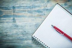 Penna rossa controllata del blocco note in bianco sul concetto di istruzione del bordo di legno Fotografia Stock Libera da Diritti