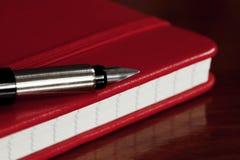 Penna rossa di fontana e del libro fotografia stock