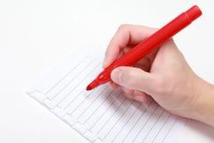 Penna rossa nella mano Fotografia Stock