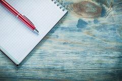 Penna a sfera controllata del blocco note in bianco sul raggiro di legno di istruzione del bordo Fotografia Stock