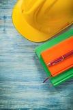 Penna a sfera dei blocchi note del casco della costruzione sul construc del bordo di legno Fotografia Stock Libera da Diritti