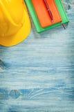 Penna a sfera dei blocchi note del casco di sicurezza sul construc del bordo di legno Immagini Stock Libere da Diritti