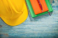 Penna a sfera dei blocchi note del casco sulla costruzione co del bordo di legno Fotografia Stock