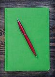 Penna a sfera del blocco note verde sul concep di legno d'annata dell'ufficio del bordo Fotografie Stock Libere da Diritti