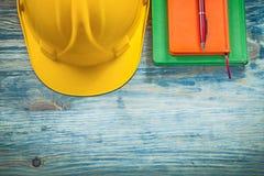 Penna a sfera protettiva dei blocchi note del casco della costruzione sul bordo di legno Fotografie Stock Libere da Diritti