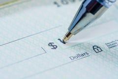 Penna som skriver dollarbelopp på kontrollen royaltyfria foton