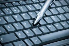 Penna sopra la tastiera del computer portatile Fotografia Stock