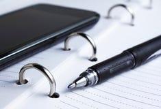 Penna, spiralanteckningsbok och mobiltelefon Royaltyfria Bilder