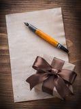 Penna stilografica attuale della carta dell'arco della scatola sul bordo di legno d'annata Fotografia Stock