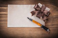 Penna stilografica attuale della carta della scatola sul concetto di festa del bordo di legno Fotografia Stock Libera da Diritti