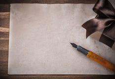 Penna stilografica della carta del contenitore di regalo sul concetto di festa del bordo di legno Fotografia Stock