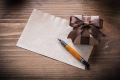 Penna stilografica della carta dell'arco del contenitore di regalo sul bordo di legno d'annata Fotografia Stock