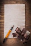 Penna stilografica della carta dell'arco di marrone del contenitore di regalo sul bordo di legno Immagini Stock Libere da Diritti